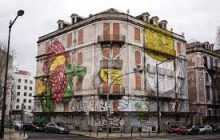 Vacant building with murals on it painted by Os Gemeos